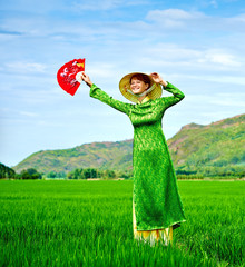 Girl in national Vietnamese dress is waving happily with veer