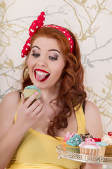 redhead girl holding a tray of colorful cupcakes.