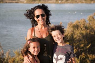 Madre e hijos con pelo al viento junto a lago