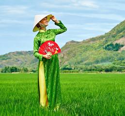 Woman walking in a rice field in traditional long dress