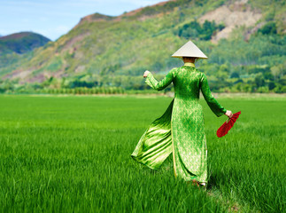 Woman walking in a rice field in traditional long dress