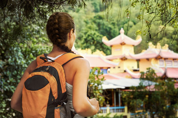 Young tourist with a backpack looking into the rainforest temple
