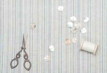 Pearl Buttons And Scissors On Natural Linen Striped Textile