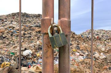 lock key on rusty fence and garbage mountain background