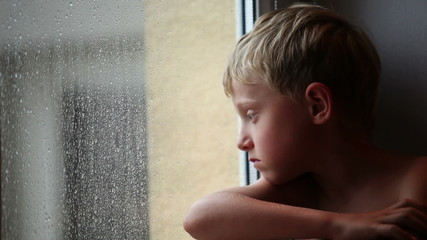 Alone little boy looks raindrops through window glass