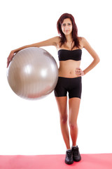 Beautiful healthy young girl with a fitness ball