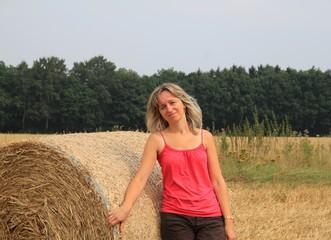 Frau steht auf Stoppelfeld neben Strohballen