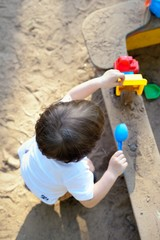 The small child plays in a sandbox with toys