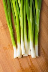 green onion on wooden board