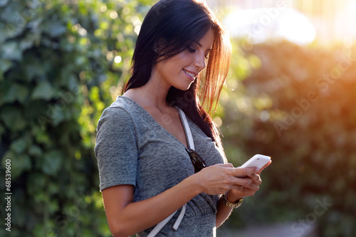canvas print picture Smiling beautiful woman texting with her phone in the garden.