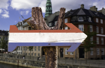 Netherlands wooden sign with a city background