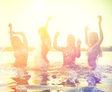Fototapety Group of happy teen girls playing at the beach on sunset