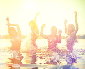 Group of happy teen girls playing at the beach on sunset