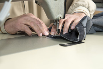 Tailor using industrial sewing machine close up