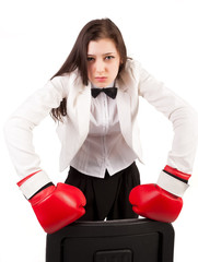 Young angry businesswoman in boxing gloves