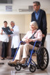 Senior woman on the wheelchair with her caregiver. Hospital back