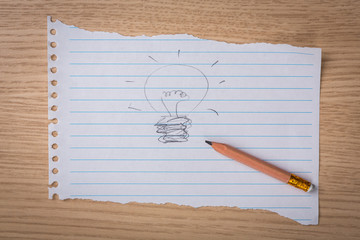 Hand drawn light bulb on paper with pencil