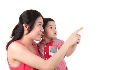 Mother holding boy  showing something isolated on white backgrou