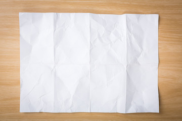White crumpled paper on a wooden desk