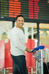 man standing in front of flight information board