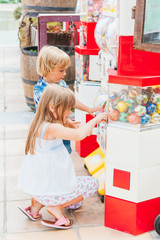 Adorable children buying balls in a toy machine