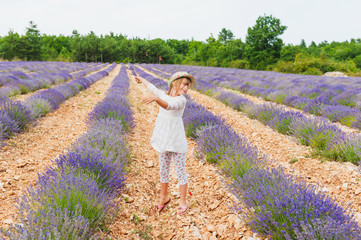 Adorable little girl playing in lavender field