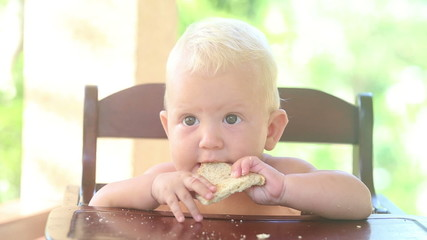baby eat bread on chear