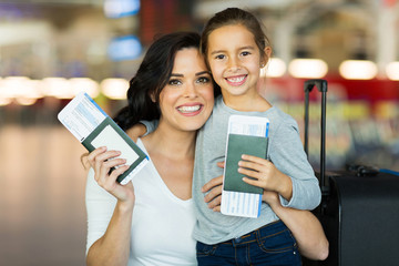 mother and daughter holding passports and boarding pass