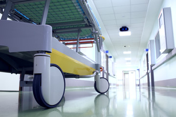 Bed on wheels waiting in the illuminated hospital corridor