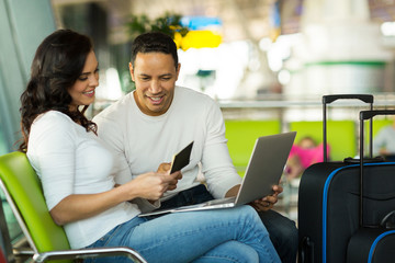 couple checking flight information on laptop