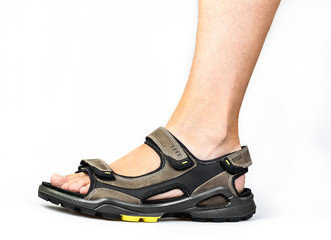 Men's foot in sandals on a white background