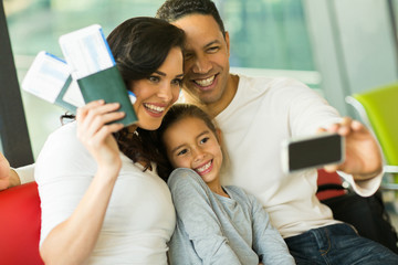 family taking selfie with smart phone at airport