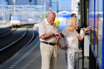 Senior traveling couple waiting for train in railway station
