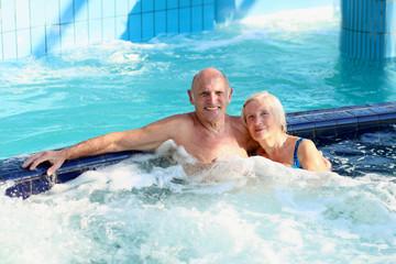 Senior couple enjoying jacuzzi in swimming pool