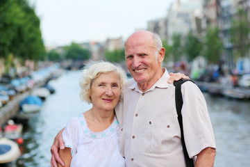 Active senior couple enjoying canal views in Amsterdam