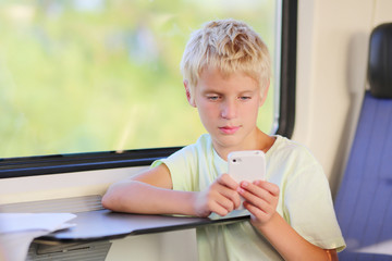 School boy texting message on his phone sitting in train