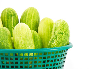 The green cucumbers in green basket on white background
