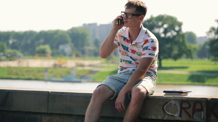 Young trendy man talking on cellphone in the city
