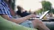 Man hands typing on modern laptop at outdoor bar