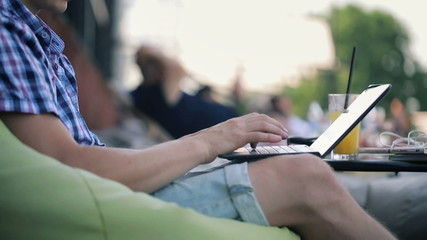 Man hands typing on modern laptop at outdoor bar
