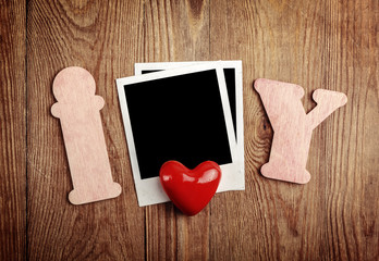 Blank instant photo and red heart on old dark grunge background