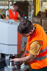 Laborer operating factory machine