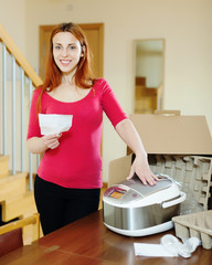 cheerful woman  reading manual for new slow cooker
