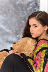 Portrait of pretty girl in sweater holding toy.