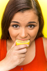 pretty girl eating fresh lemon.