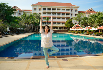 middle aged woman doing fitness stretching by pool in hotel