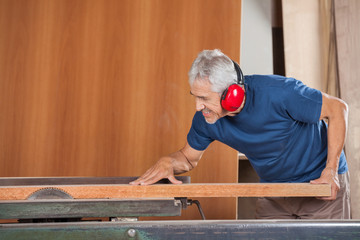 Senior Male Carpenter Cutting Wooden Plank With Tablesaw