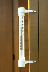 Outdoor thermometer hanging on wooden wall closeup