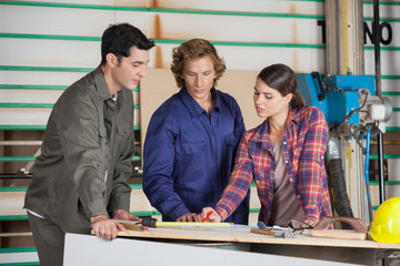 Carpenters Discussing At Table In Workshop