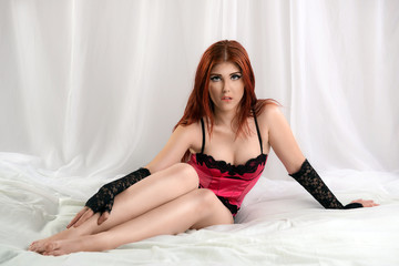 Sensual woman sitting in the bed and biting her lips
